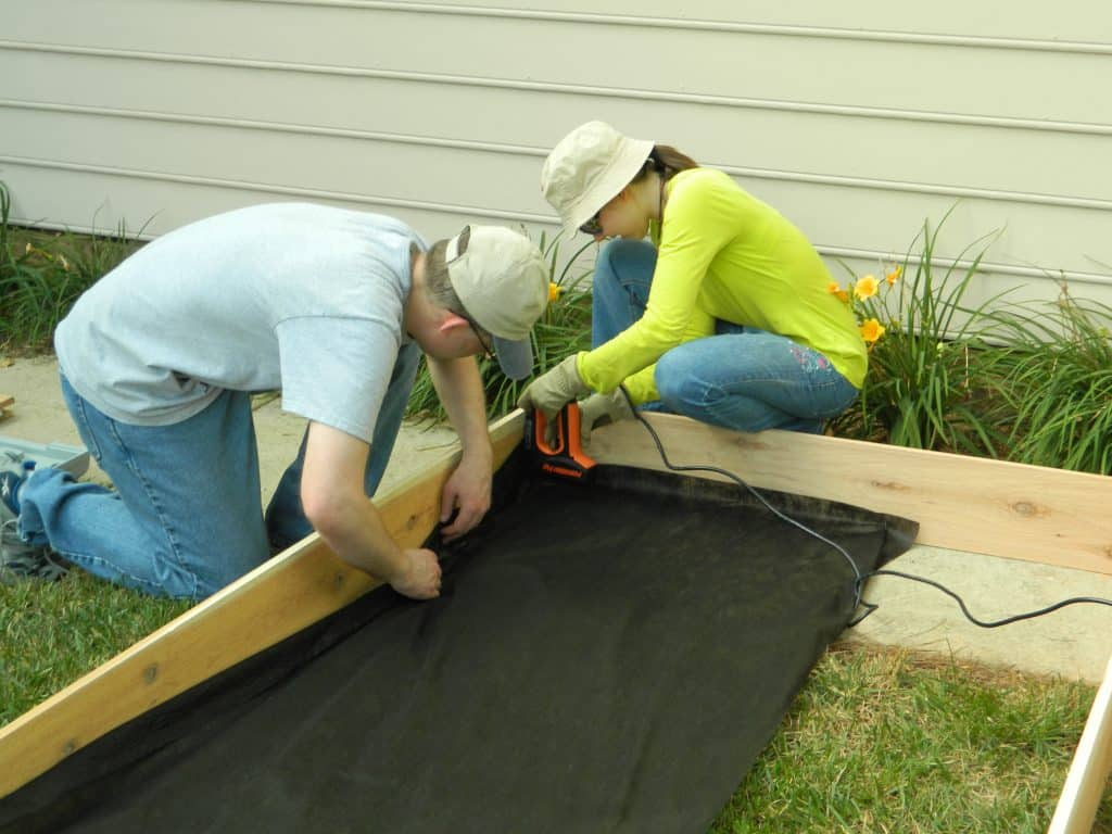 Want to make your own DIY Raised Garden Bed? This step-by-step tutorial will help get your garden up and growing in no time! width=