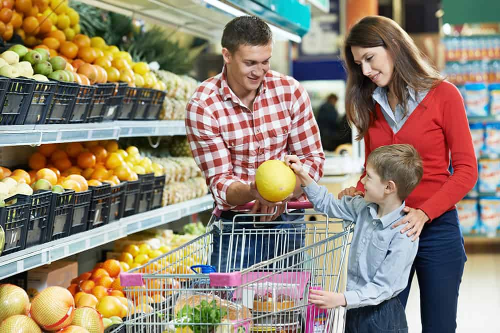 family deciding on melon at grocery store