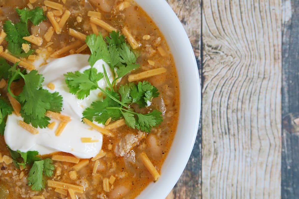 Need a hearty and healthy dish for the colder months? This Slow Cooker White Bean Turkey Chili recipe is super easy and ready in less than three hours!